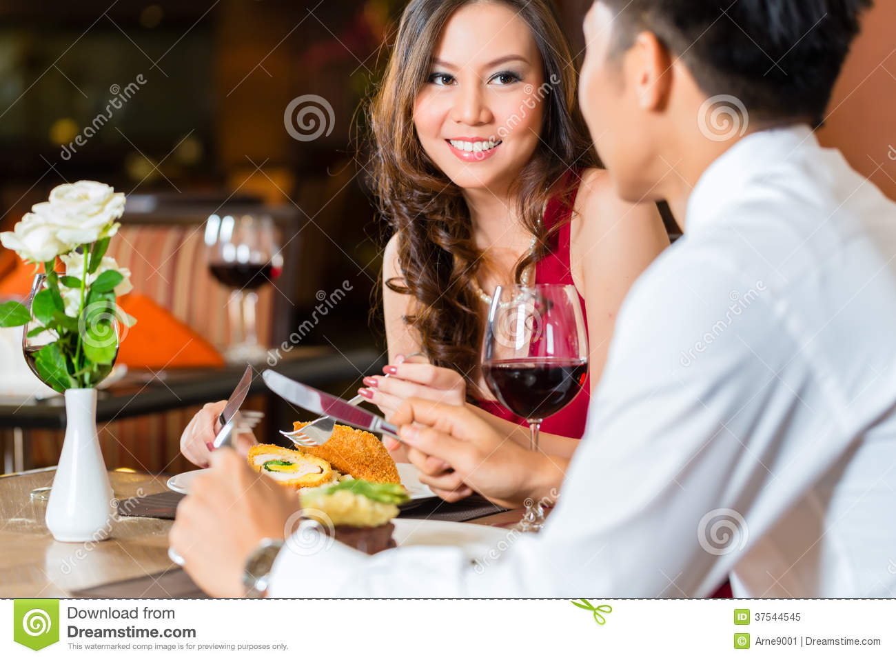 Chinese couple having romantic dinner in fancy restaurant