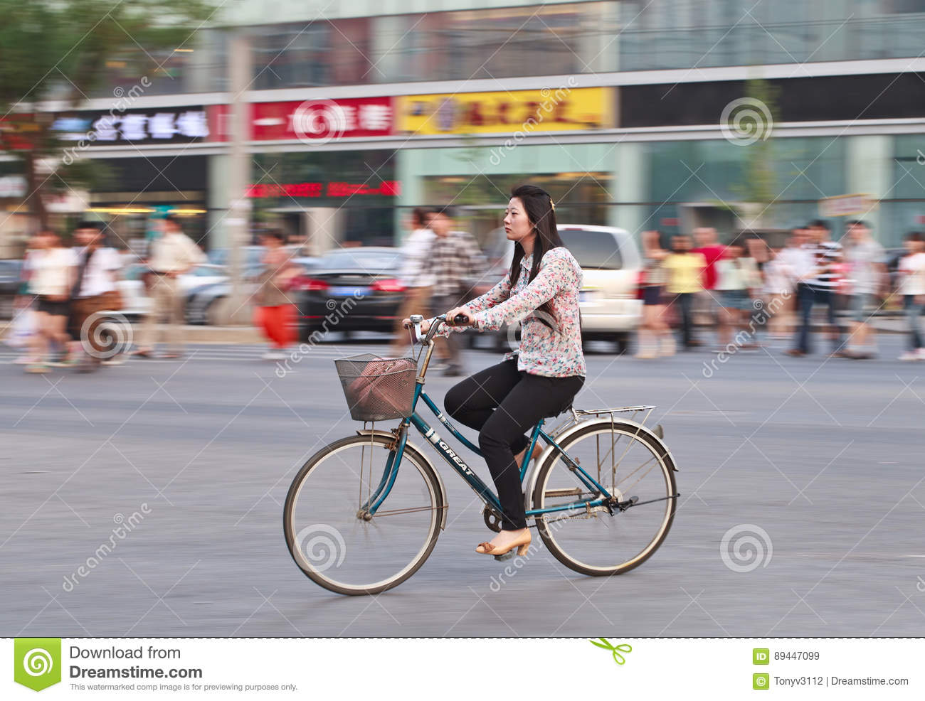 Chinese Girl On A Bicycle With Shops On The Background Beijing
