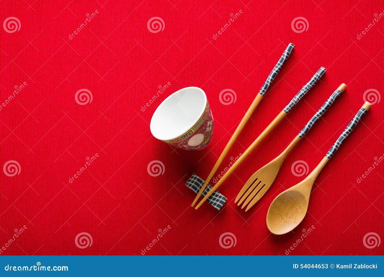 Chinese kom, vork, lepel en eetstokjes op rode mat