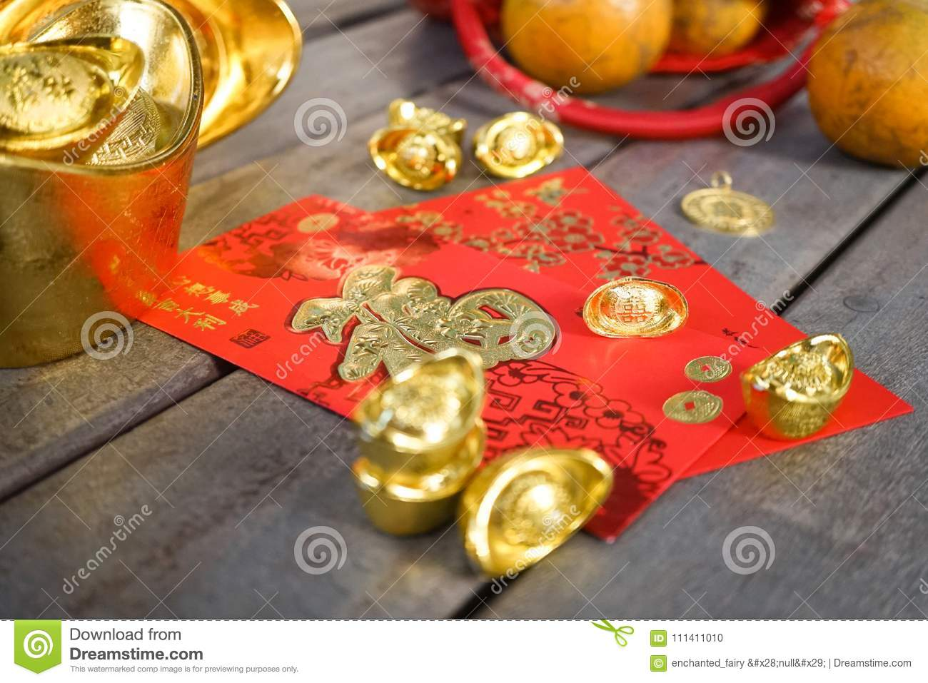 Chinese New Year ornaments with oranges, gold ingots and red envelopes or hong pao on wood background. Selective focus. Chinese
