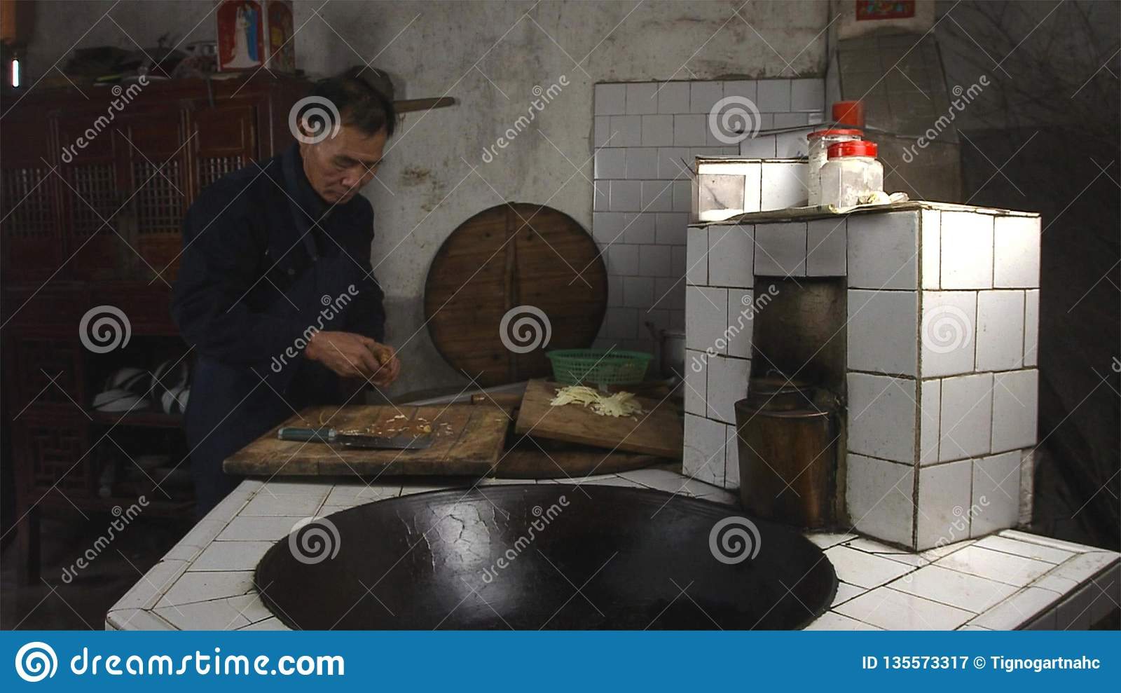 Chinese old man cooking in kitchen at his home countryside. Yunnan. China.