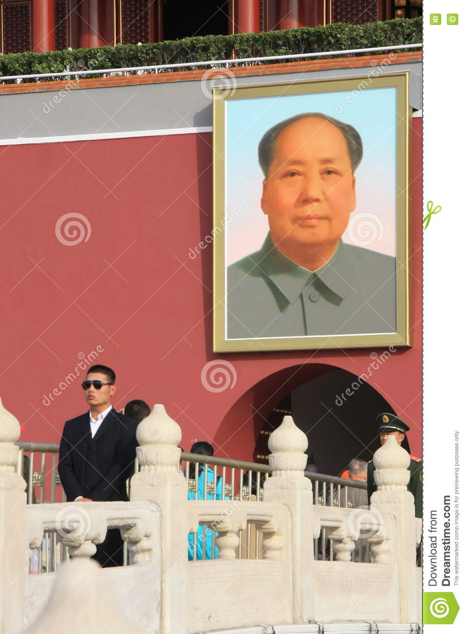 Chinese security officer on the background of a portrait of Mao Zedong