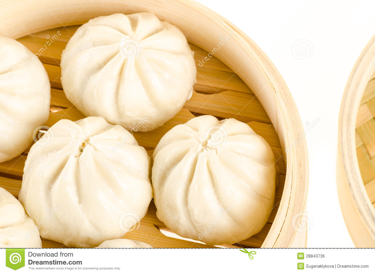 Chinese steamed buns in bamboo steamer basket isolated on white.