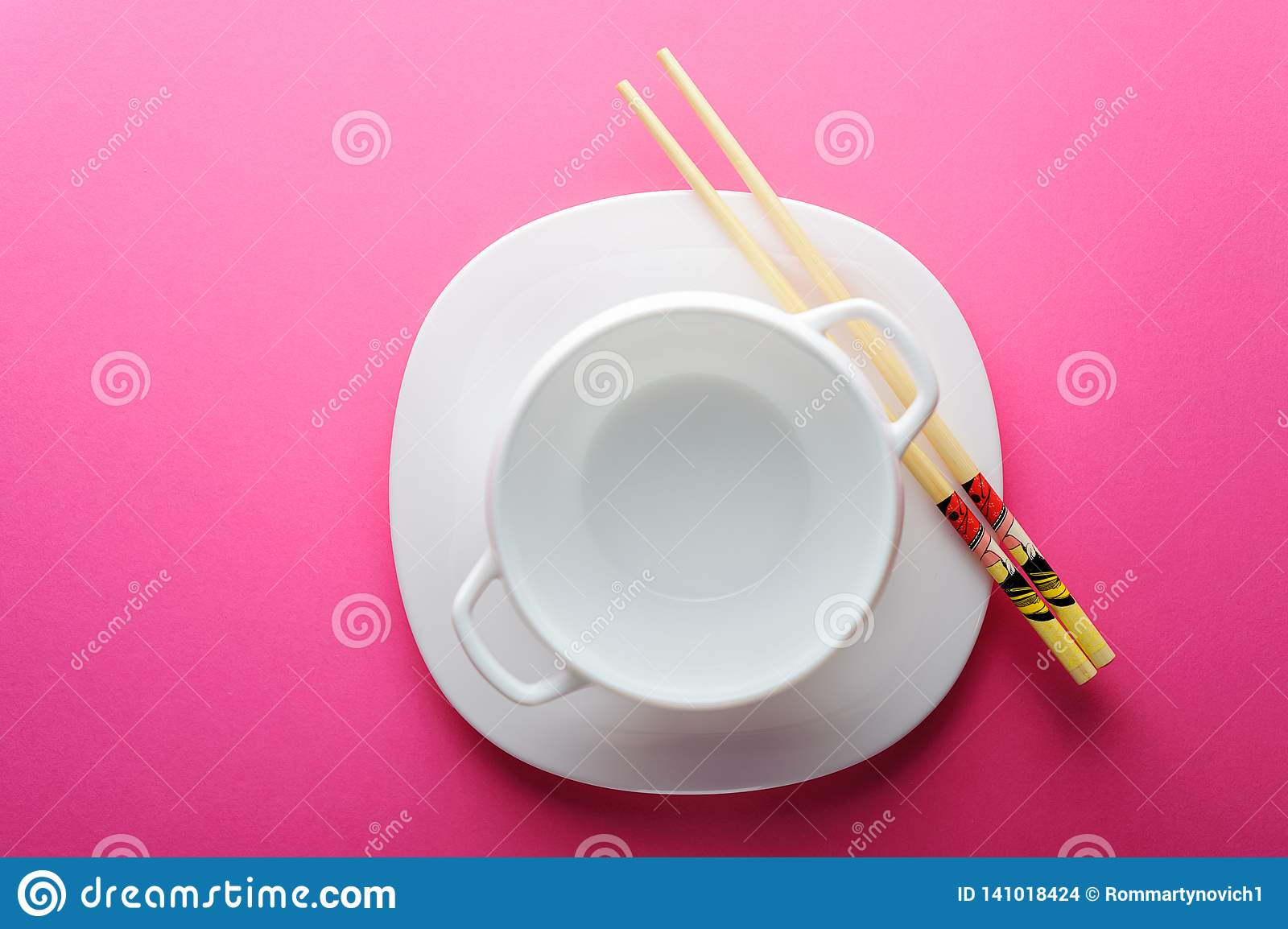 Chinese sticks white plate on a pink background