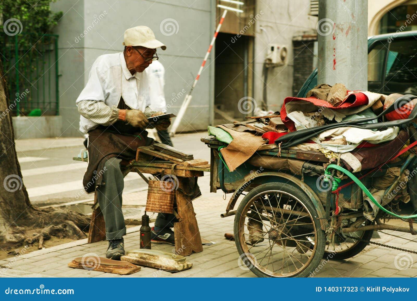 Beijing, China - June 10, 2018: Chinese elderly man repairs shoes on the street of Beijing.