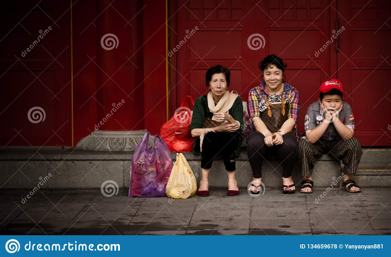 Chinese tourists sitting and waiting in Singapore street