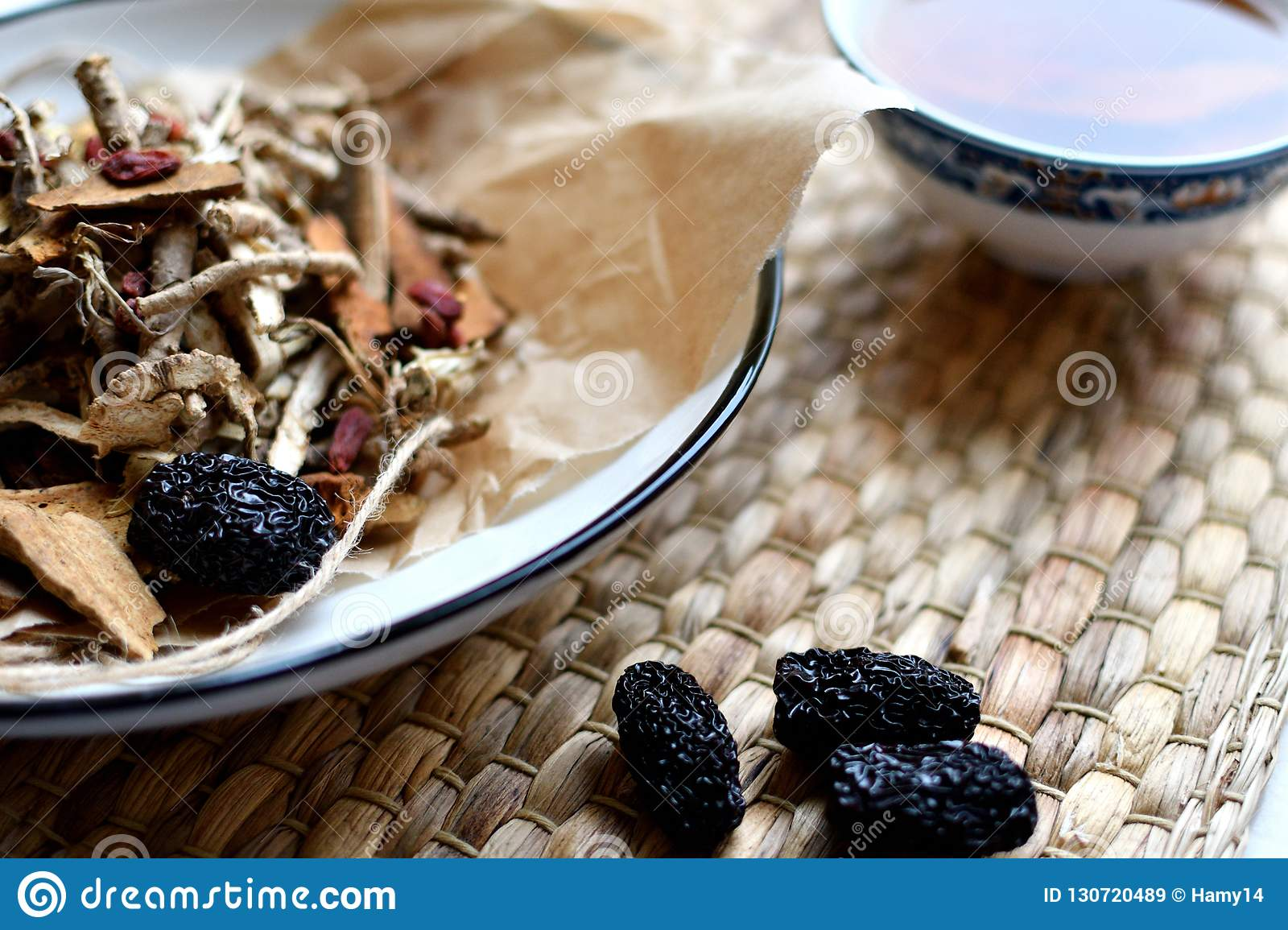 Chinese traditional medicine script. Herbal tea with jujubes, goji berries, gingseng roots and others on parchment paper on neutra