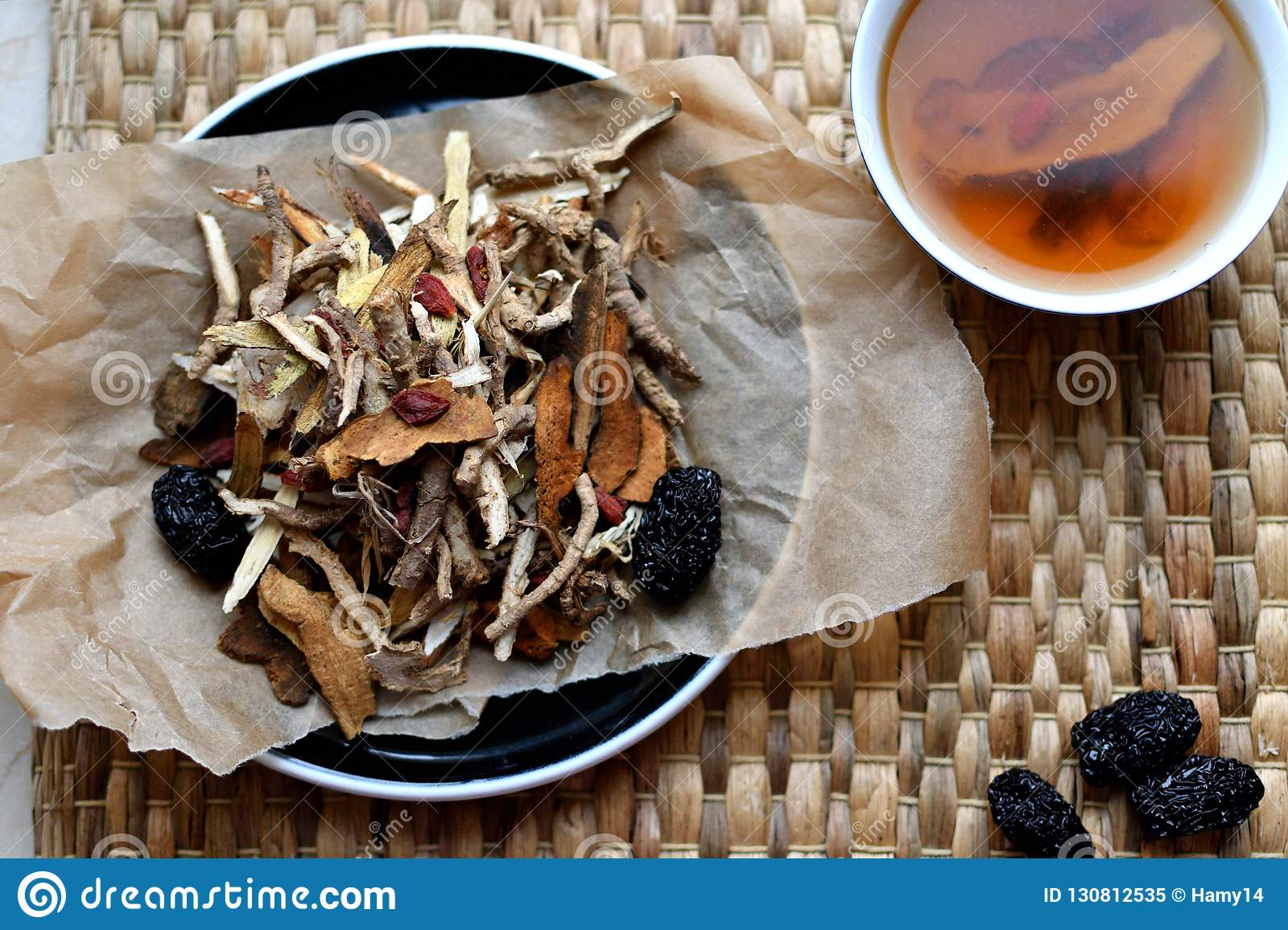Chinese traditional medicine script. Herbal tea with jujubes, goji berries, gingseng roots and others on parchment paper on neutr