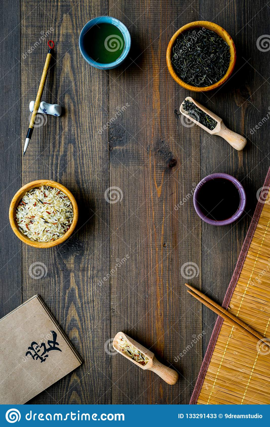 Chinese traditional symbols concept. Tea, rice, hieroglyph love, bamboo table mat, chopsticks, soy sause on dark wooden