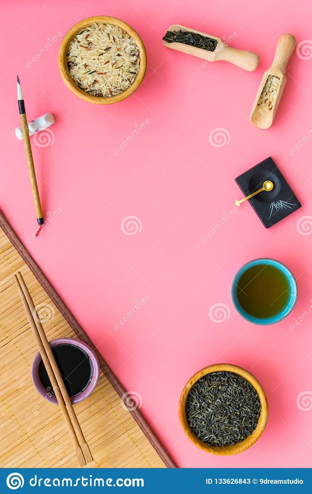 Chinese traditional symbols concept. Tea, rice, hieroglyph love, bamboo table mat, chopsticks, soy sause on pink