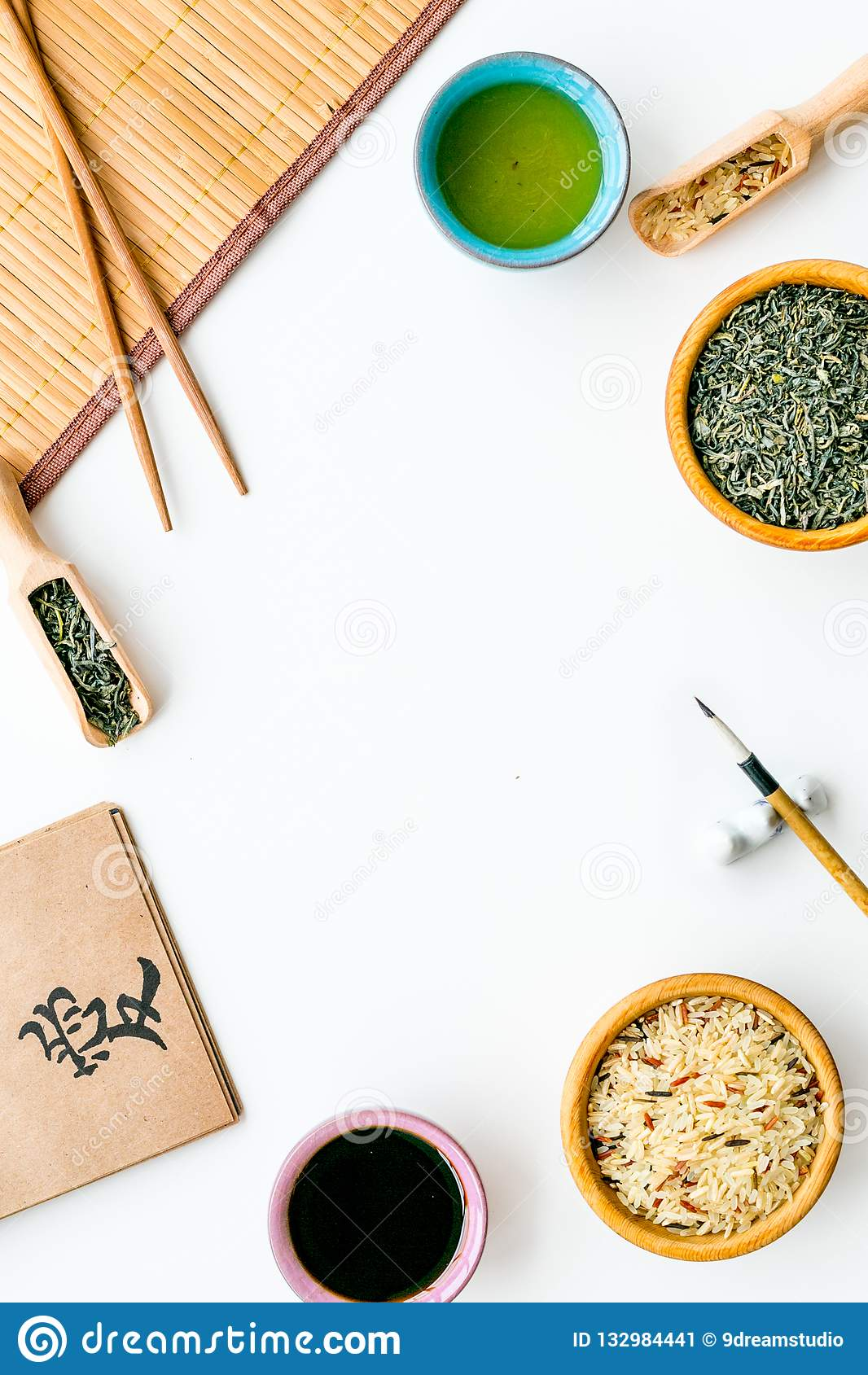 Chinese traditional symbols concept. Tea, rice, hieroglyph love, bamboo table mat, chopsticks, soy sause on white