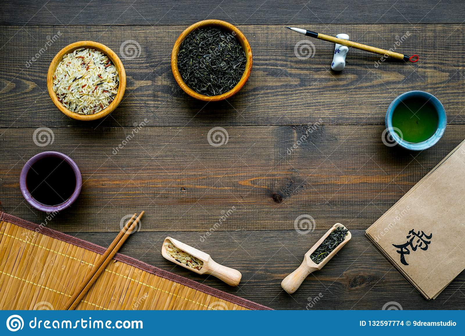 Chinese traditional symbols concept. Tea, rice, hieroglyph love, bambootabe mat, chopsticks, soy sause on dark wooden