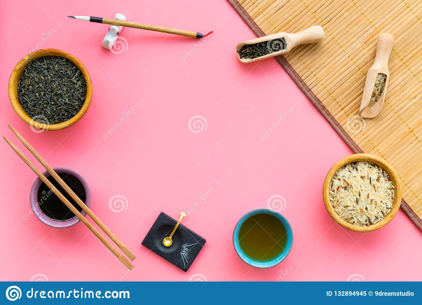 Chinese traditional symbols concept. Tea, rice, hieroglyph love, bambootabe mat, chopsticks, soy sause on pink