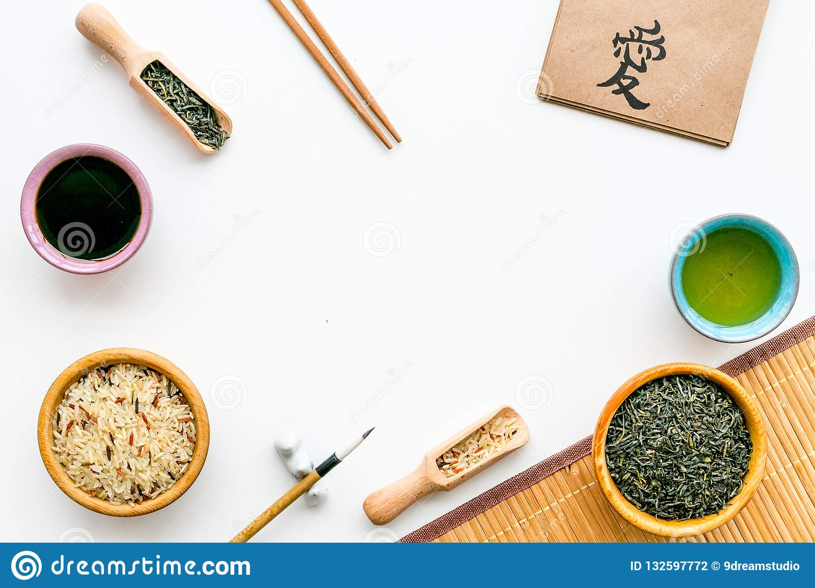 Chinese traditional symbols concept. Tea, rice, hieroglyph love, bambootabe mat, chopsticks, soy sause on white