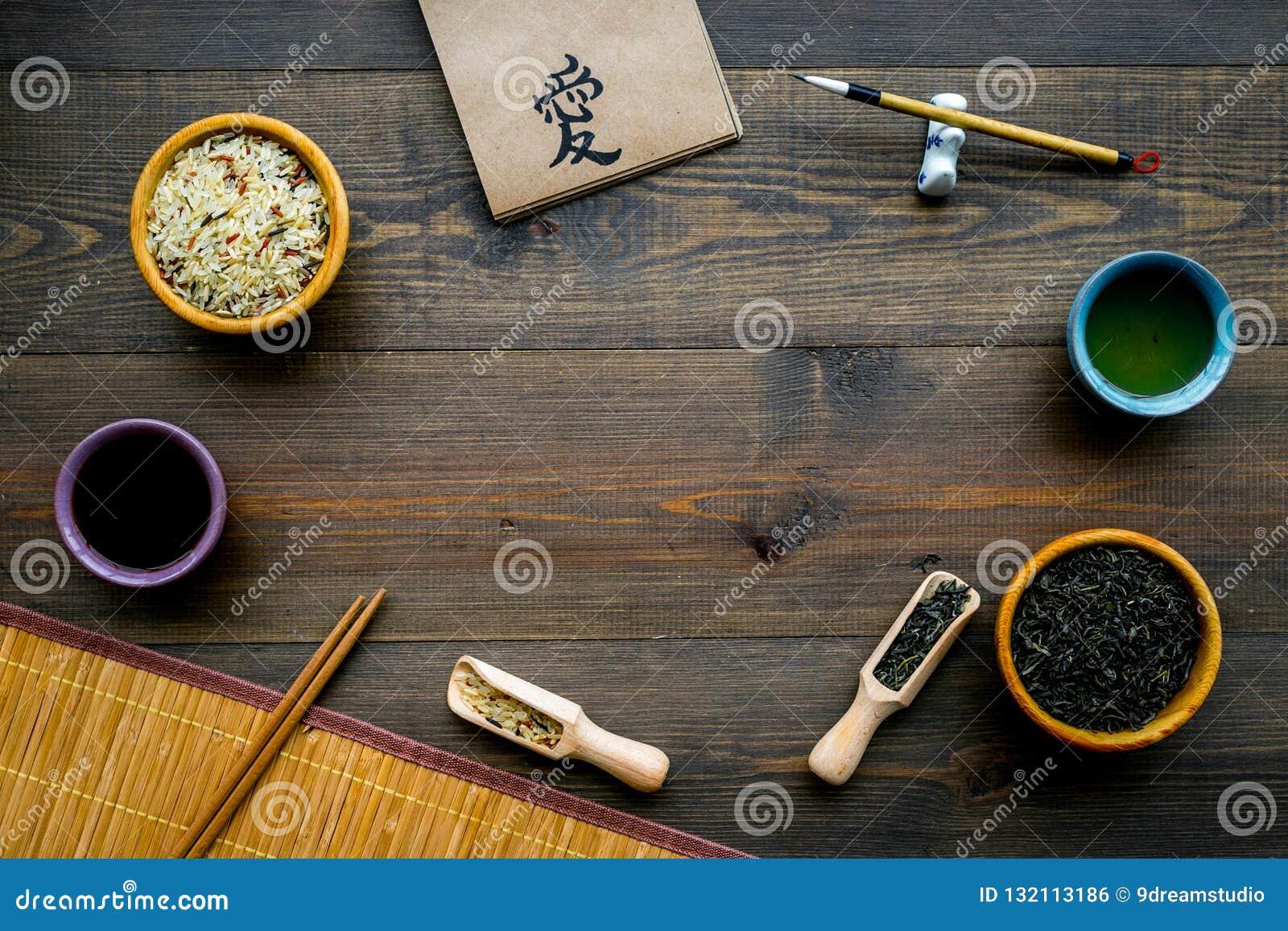 Chinese traditional symbols concept. Tea, rice, hieroglyph symbol, bambootabe mat, chopsticks, soy sause on dark wooden