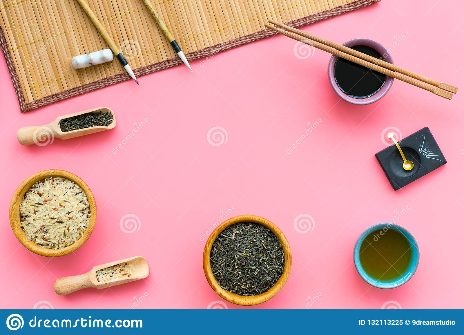Chinese traditional symbols concept. Tea, rice, hieroglyph symbol, bambootabe mat, chopsticks, soy sause on pink