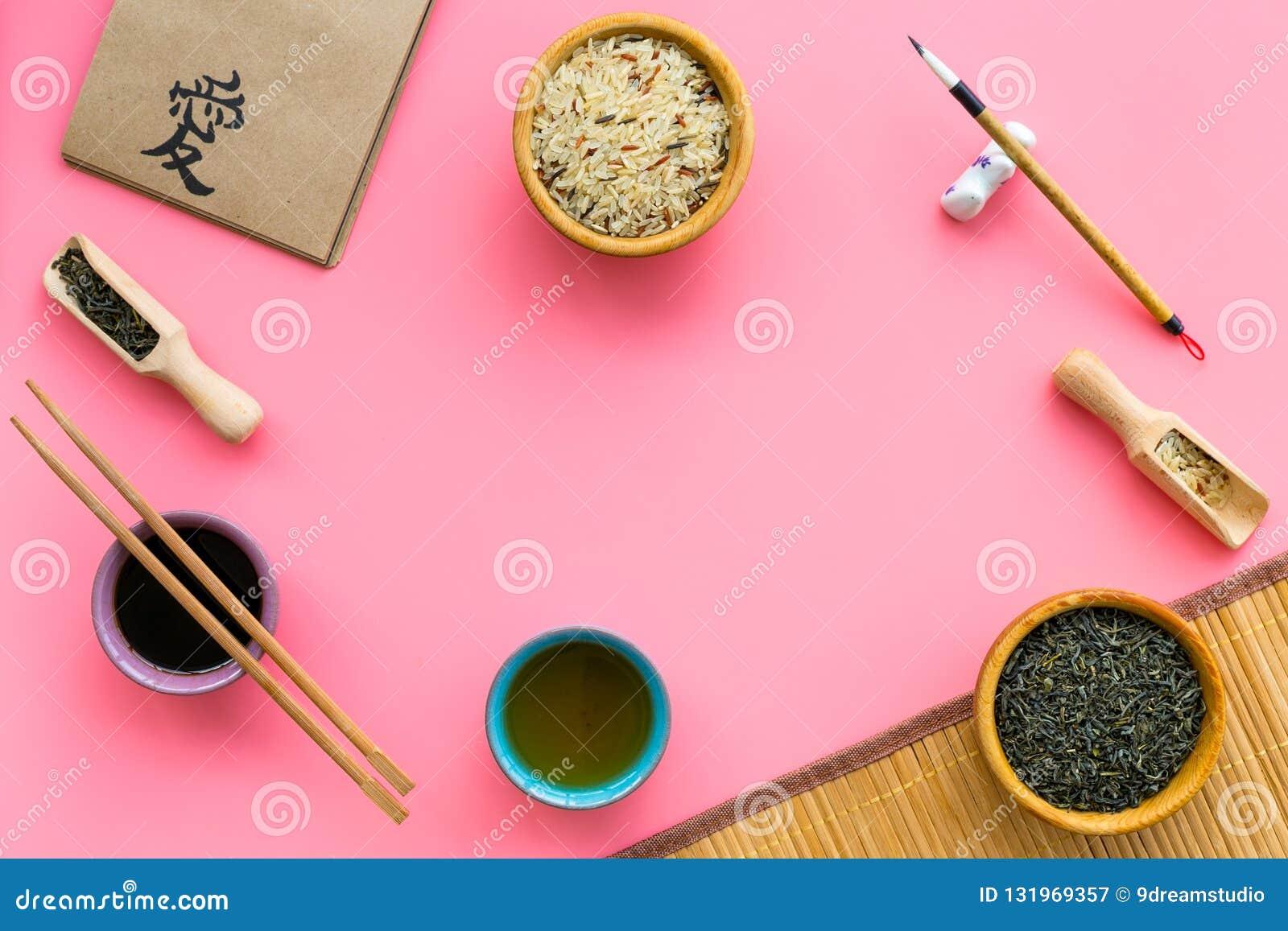 Chinese traditional symbols concept. Tea, rice, hieroglyph symbol, bambootabe mat, chopsticks, soy sause on pink