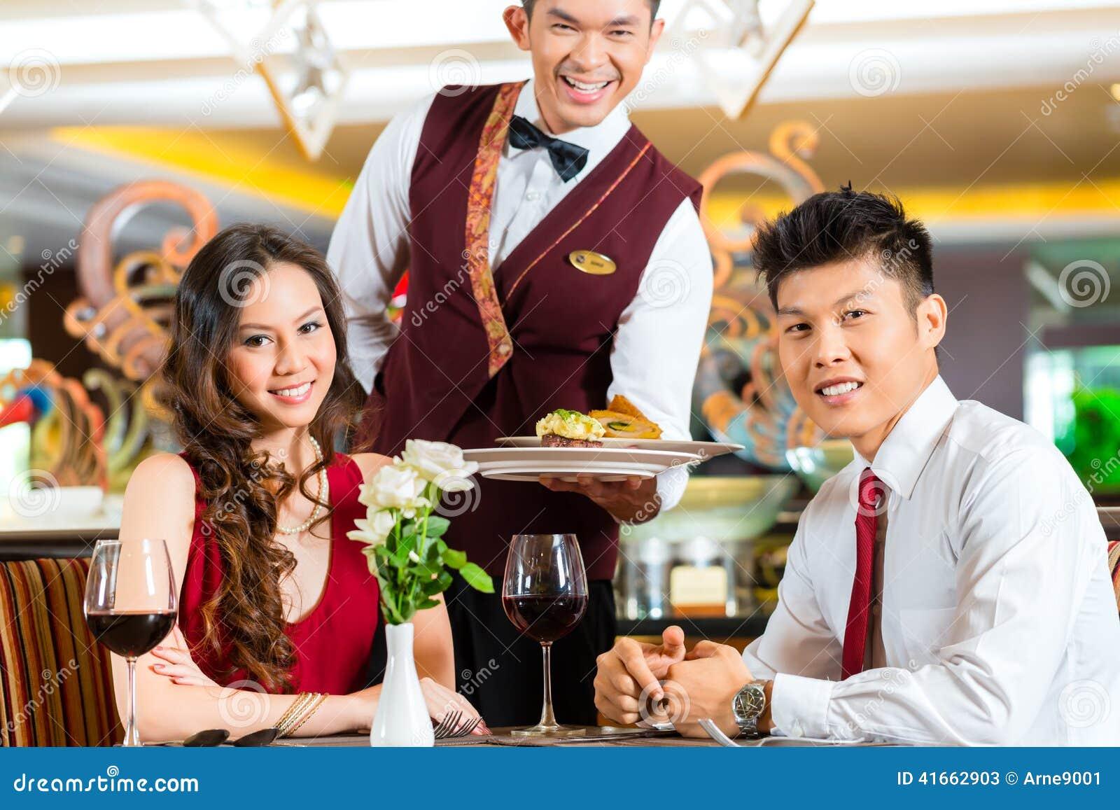 Chinese Waiter Serving Dinner In Elegant Restaurant Or