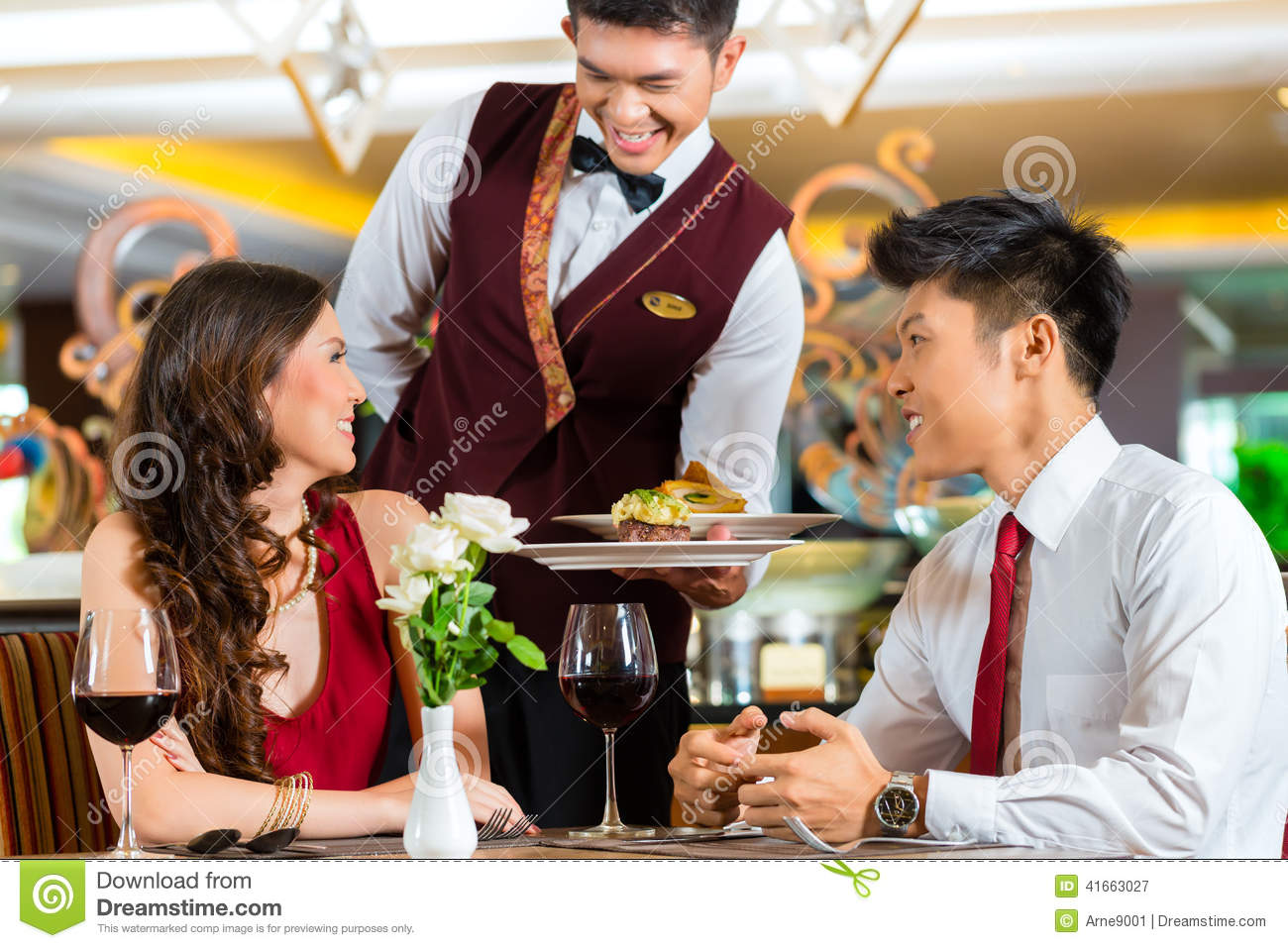Chinese Waiter Serving Dinner In Elegant Restaurant Or