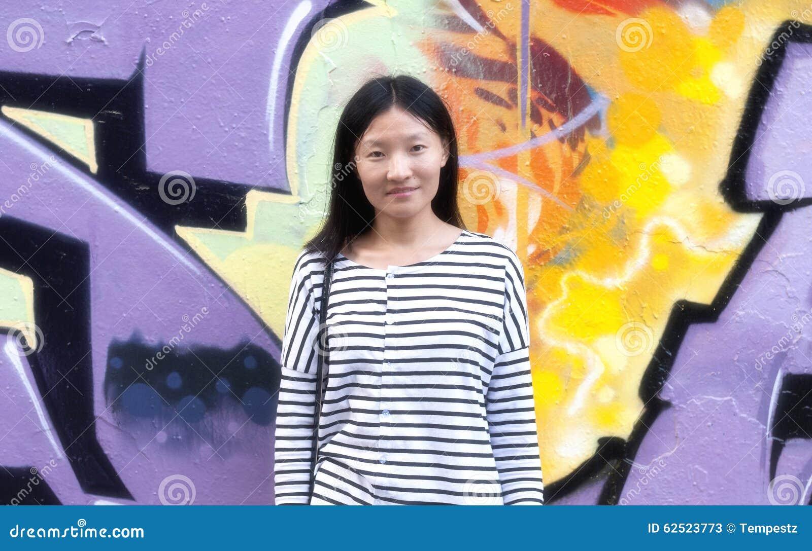 Chinese woman against urban art wall
