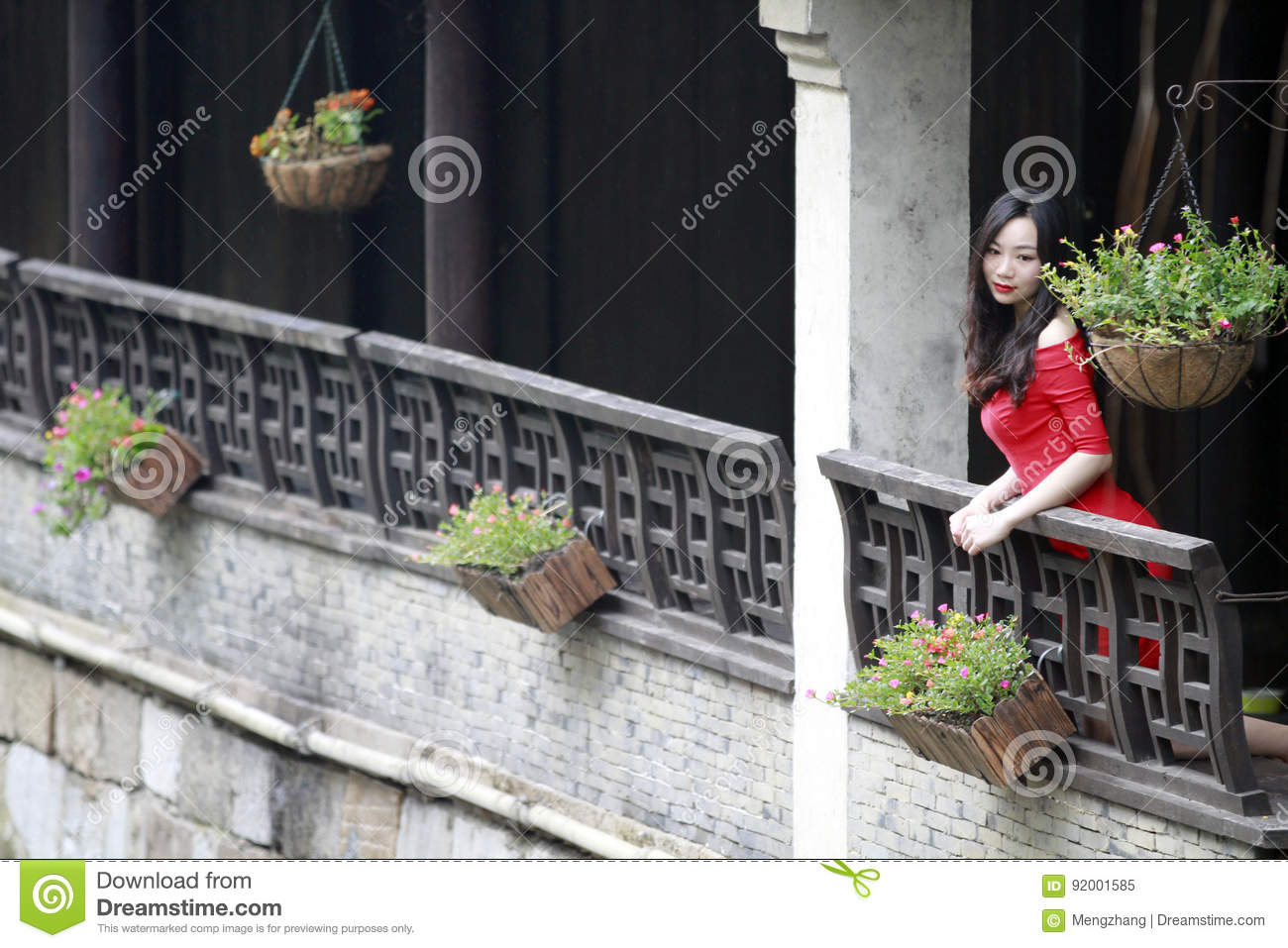 A Chinese woman in red dress in Feng Jing ancient town