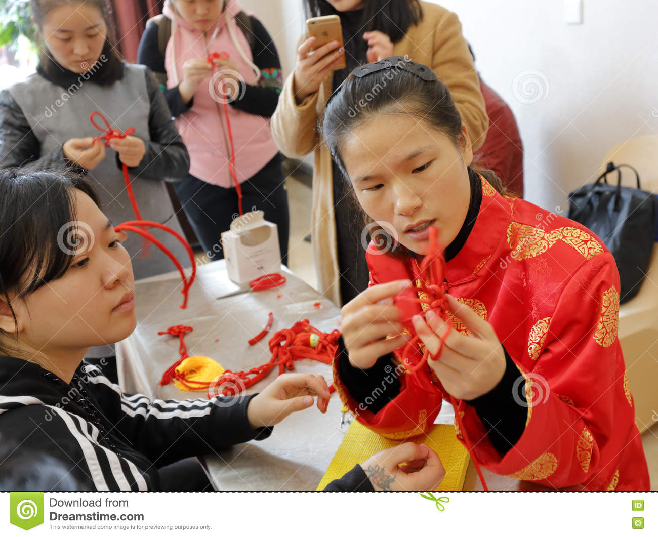 Chinese women learn to do chinese lucky knotting