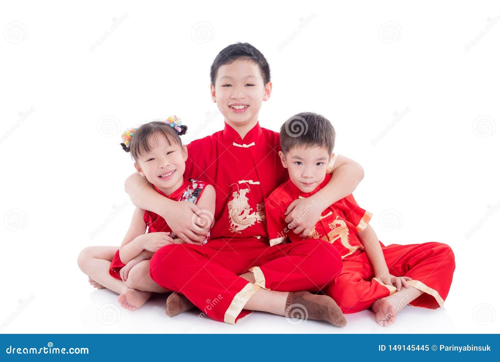 Chinesische Kinder, die traditionelles Kostümsitzen und -lächeln auf dem Boden tragen