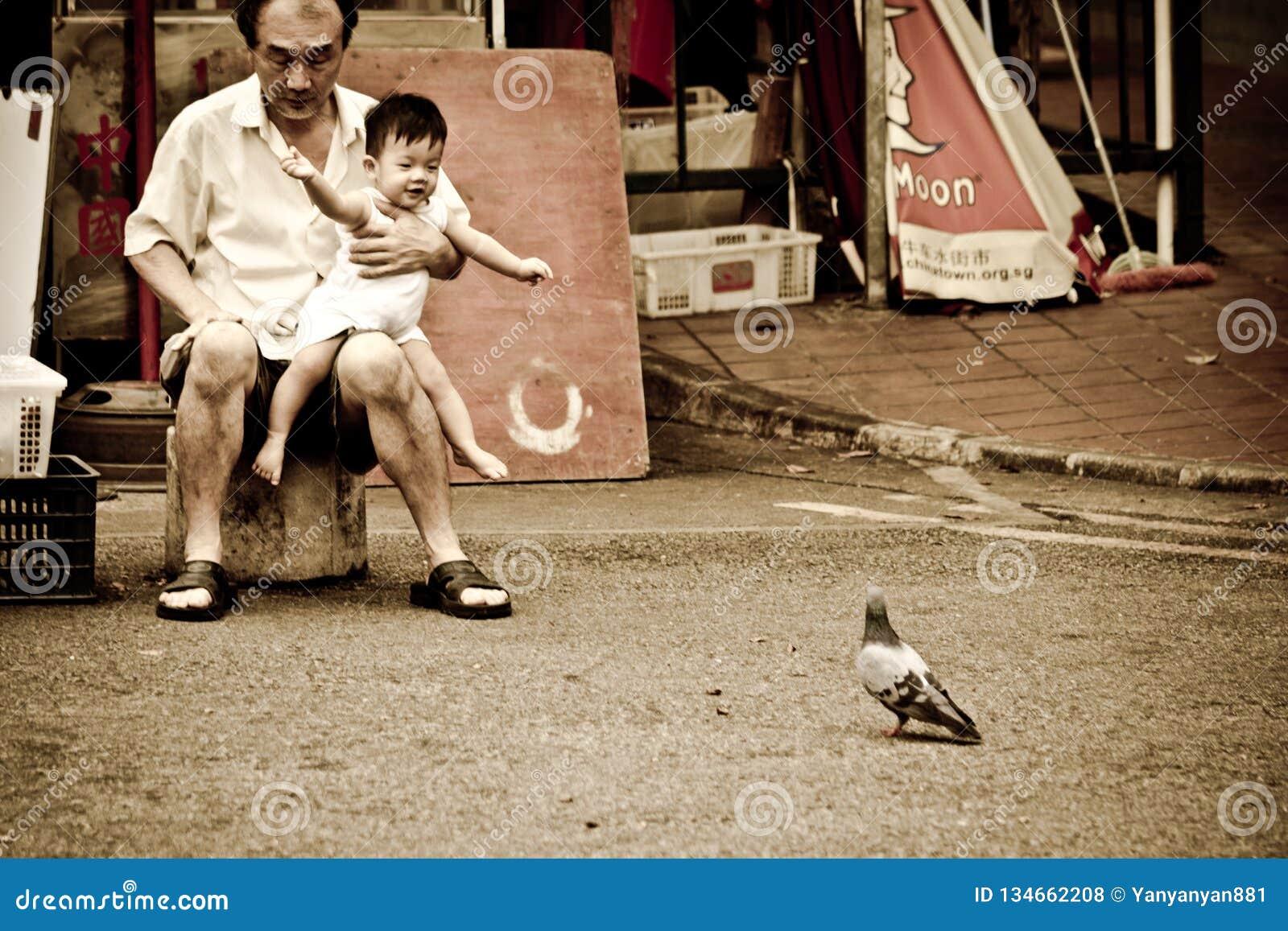 Chinesischer Mann trägt ein Kind, das durch einen Vogel aufgeregt wird
