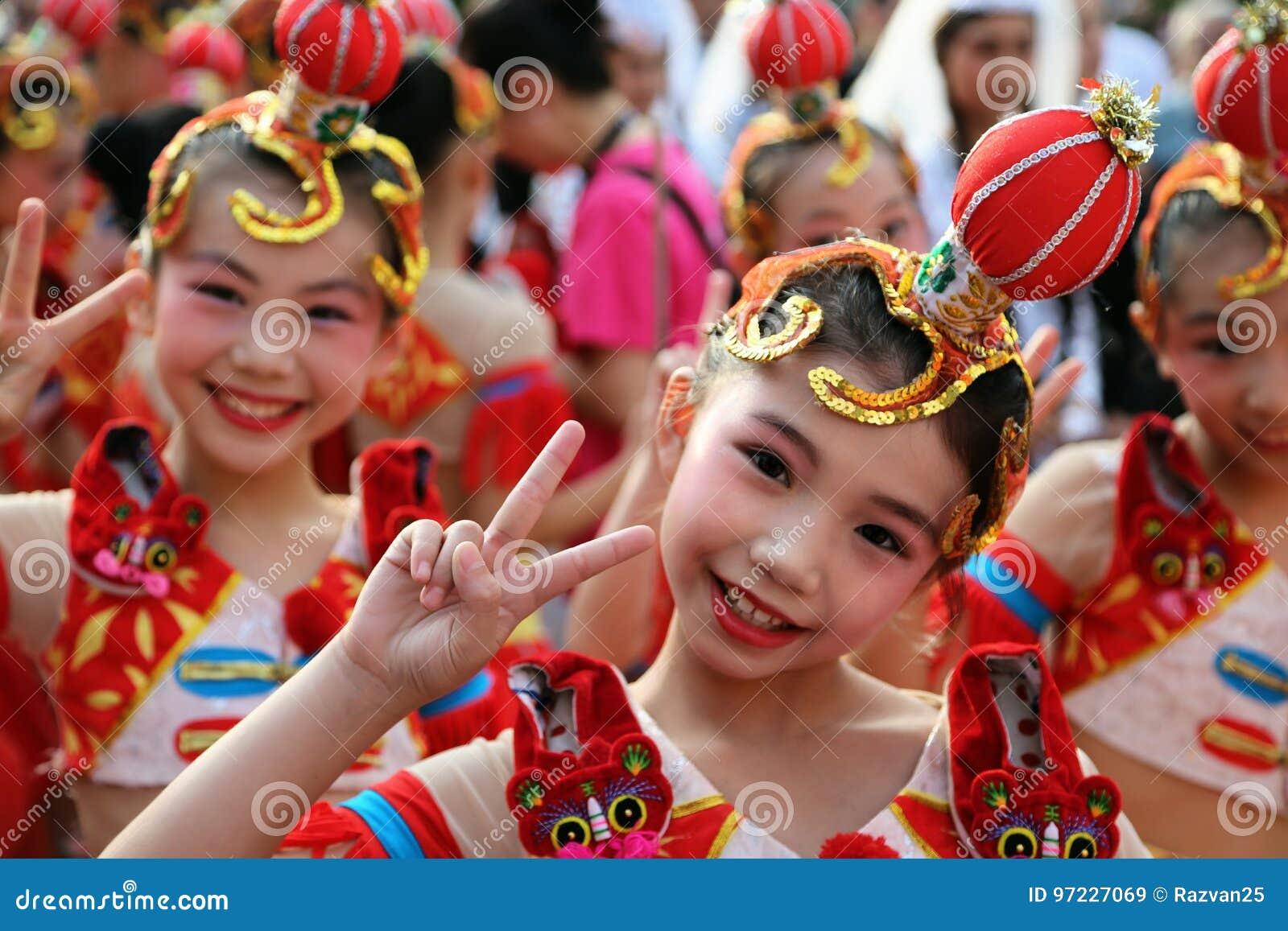 Chinesischer Tänzer im traditionellen Kostüm am internationalen Folklore-Festival für Kinder und Jugend-goldene Fische