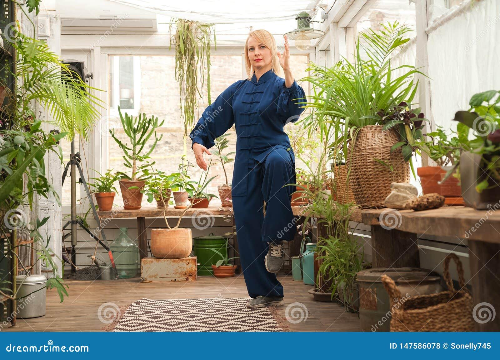 Chinesisches Kampfk?nste tai-Chi Frau, die Taijiquan-Disziplin in einem Gew?chshaus mit Blumen ?bt