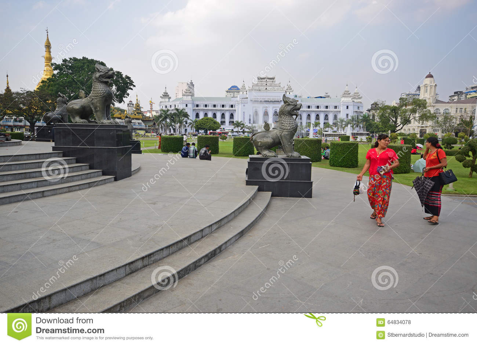 Chinthe雕象在有美丽的妇女的仰光缅甸在前面的红色的&寺庙&殖民地大厦在背景中
