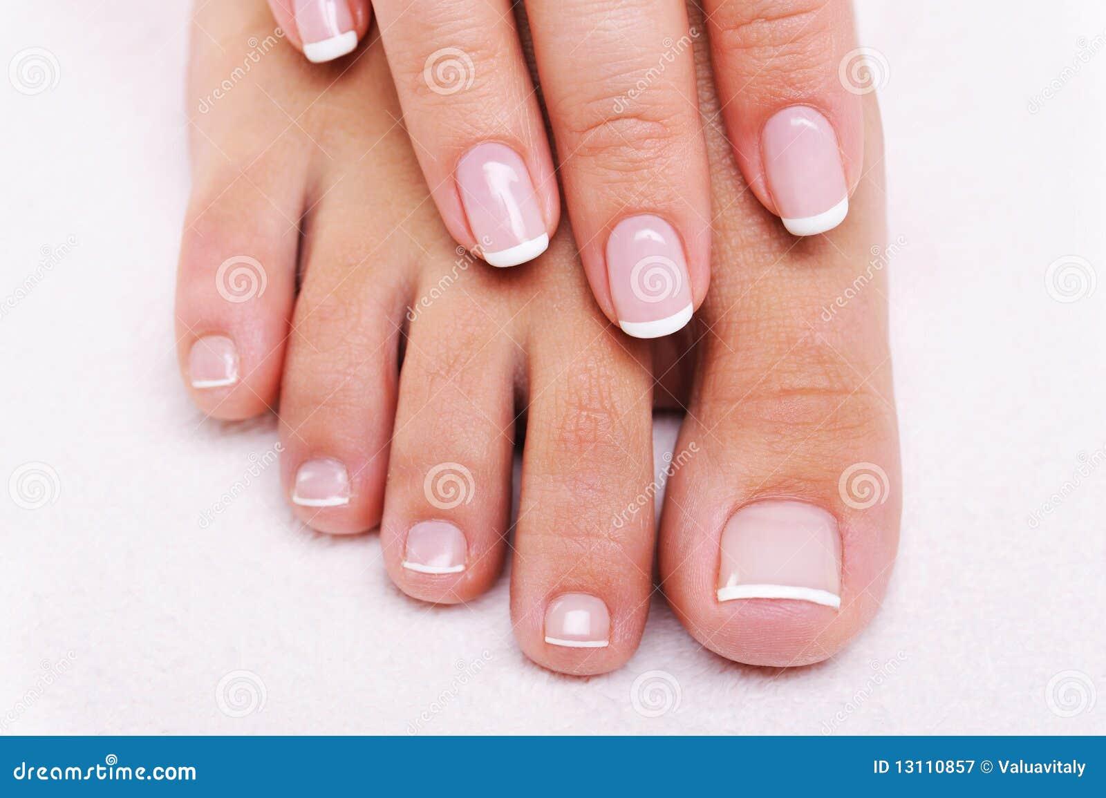 Chiodi di bellezza di una mano femminile e dei piedi
