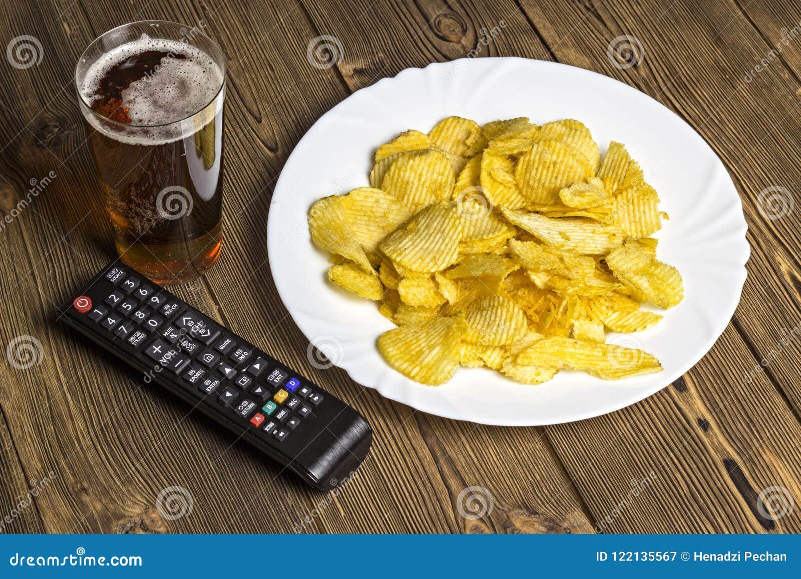 Chiper med öl och TVfjärrkontroll på en träbakgrundsfjärrkontroll