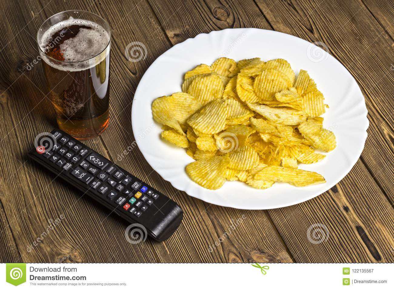 Chips with beer and TV remote control on a wooden background remote