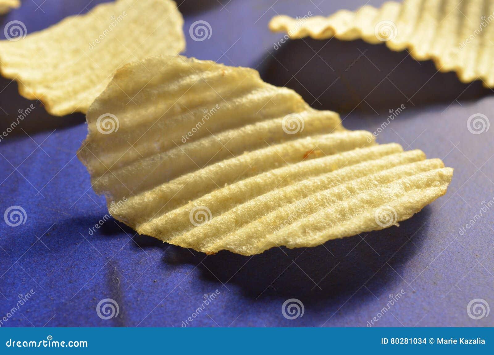 Chips met geribbeld of golven op blauwe oppervlakte