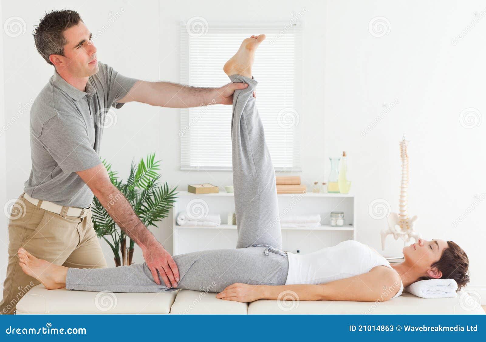 Chiropracticus het uitrekken zich het been van een wijfje