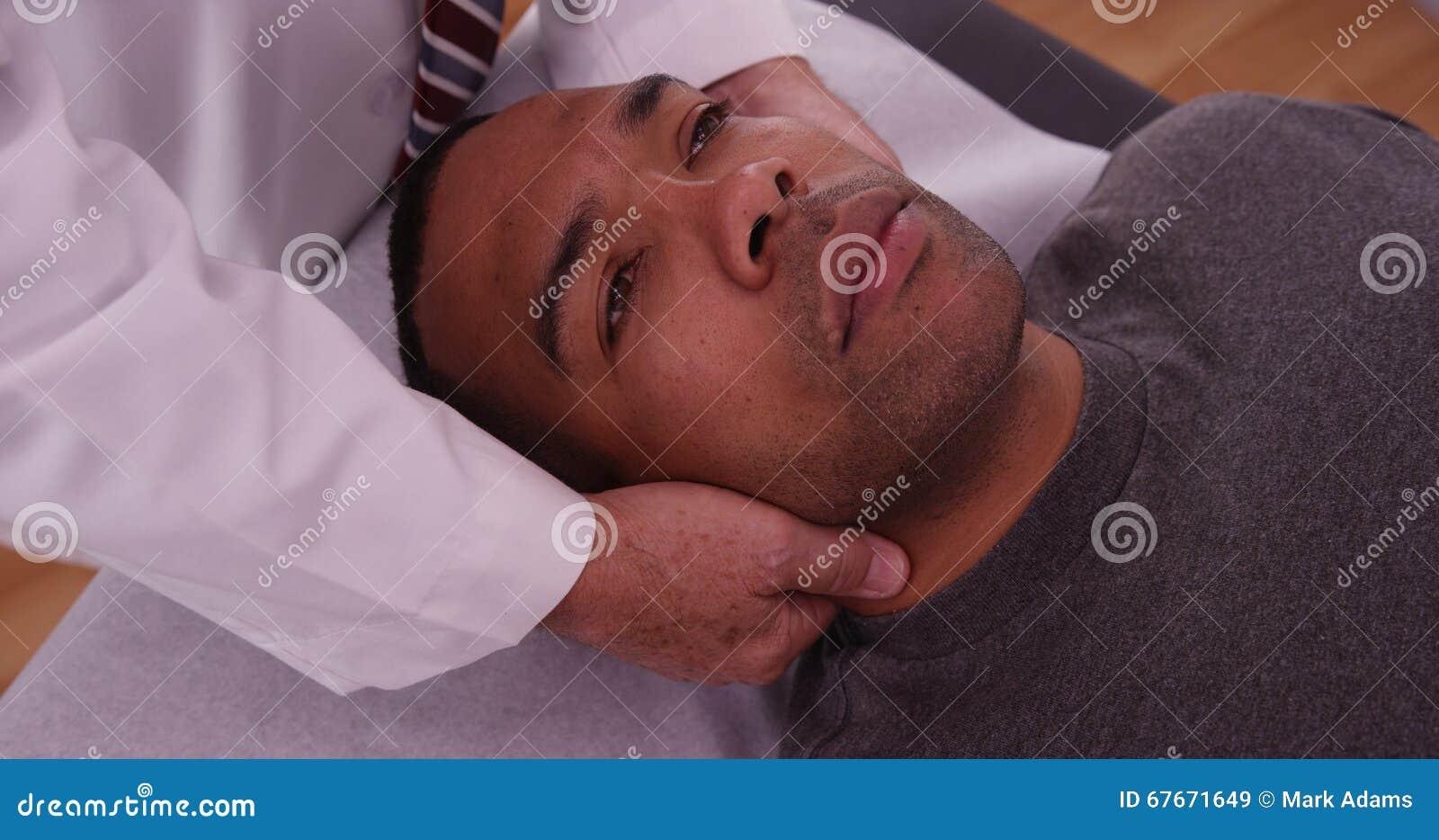 Chiropractor που ελέγχει τον τραυματισμό λαιμών του αφρικανικού αρσενικού ασθενή