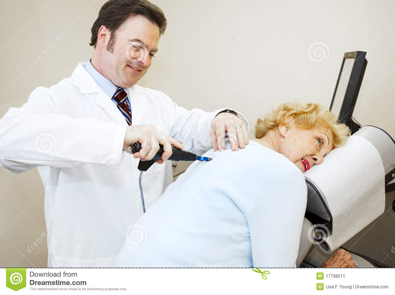 Friendly, smiling chiropractor adjusting a senior woman's back.