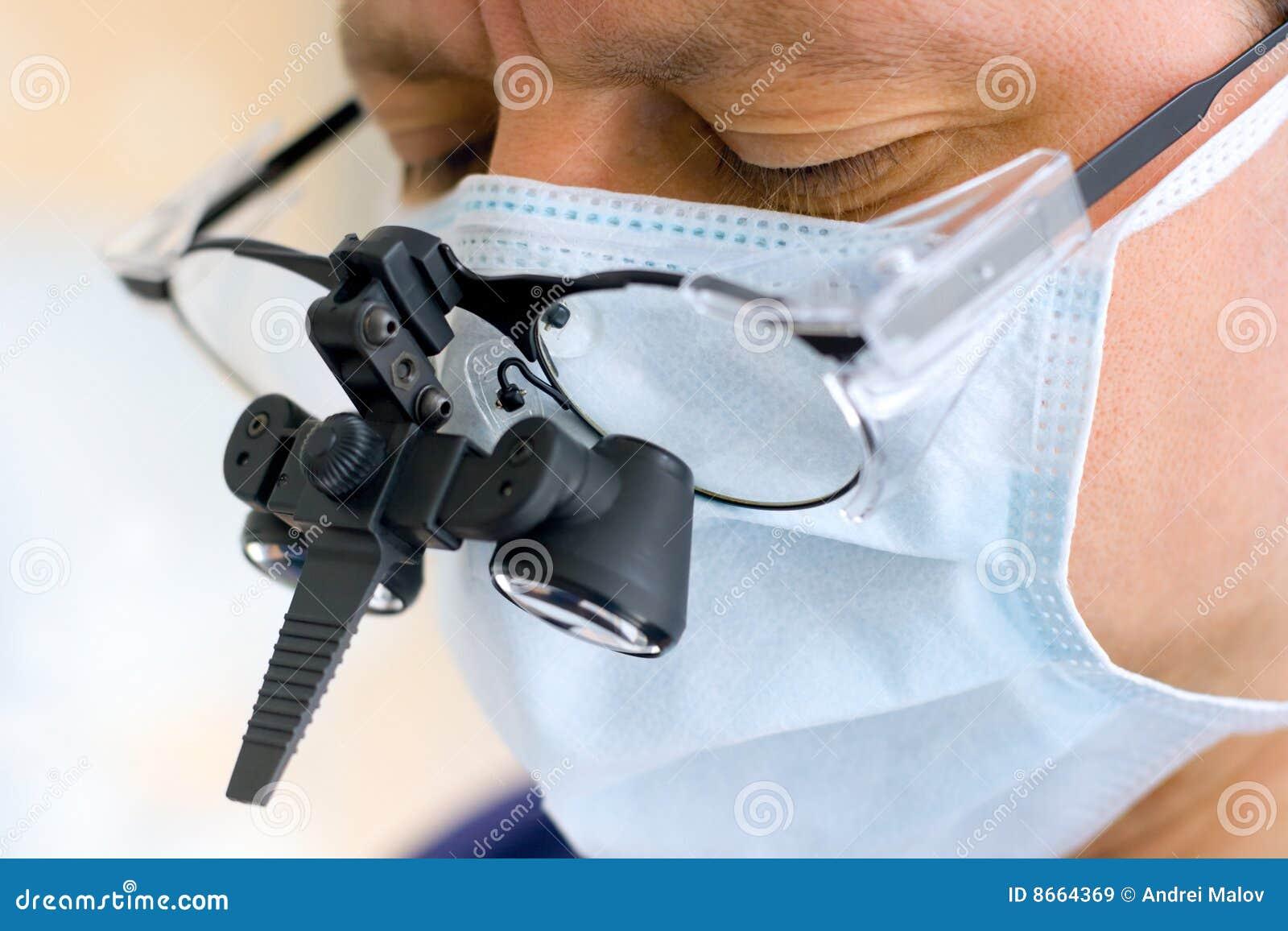 Chirurg met binoculaire glazen