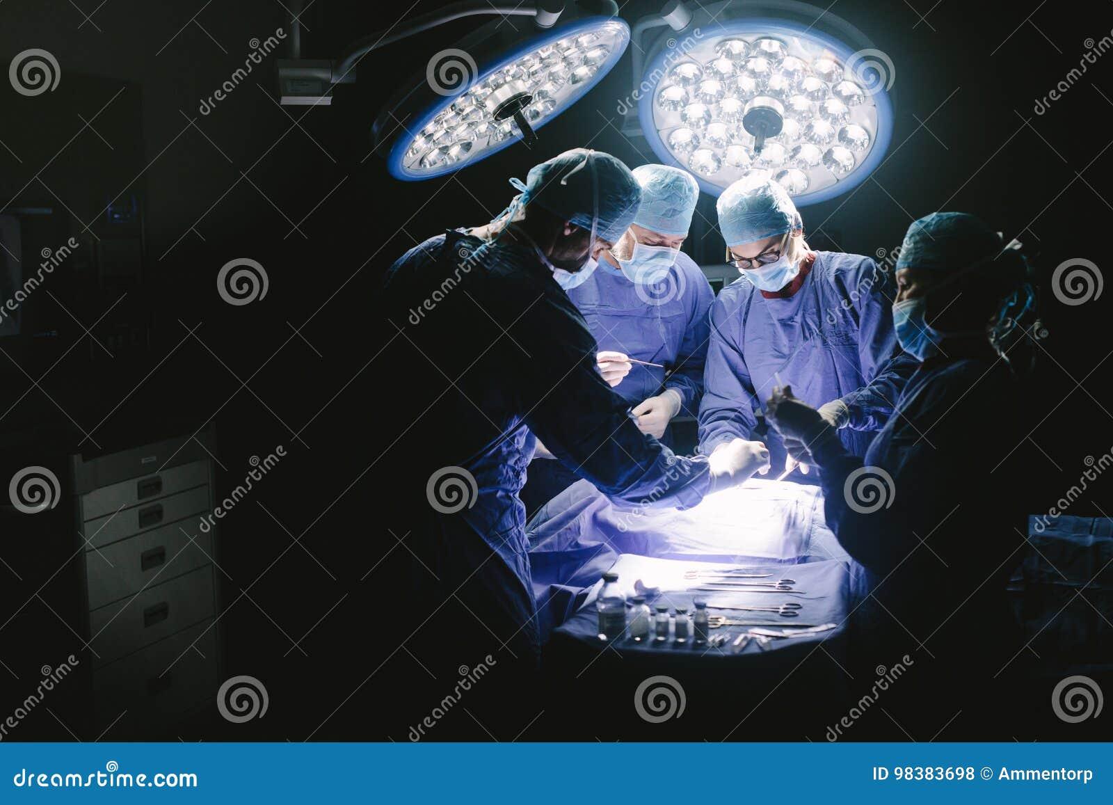 Chirurgen die chirurgische procedure in werkend theater uitvoeren