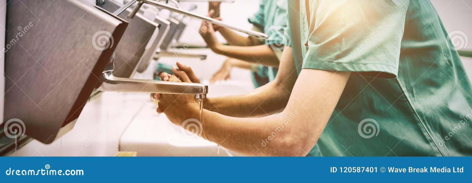 Chirurgen, die ihre Hände beim Lächeln waschen