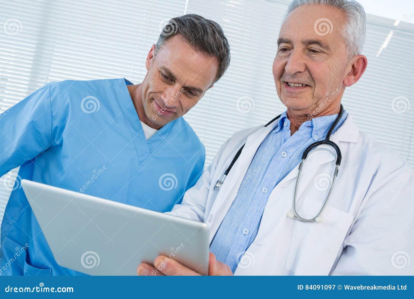 Chirurgien et docteur discutant au-dessus du comprimé numérique