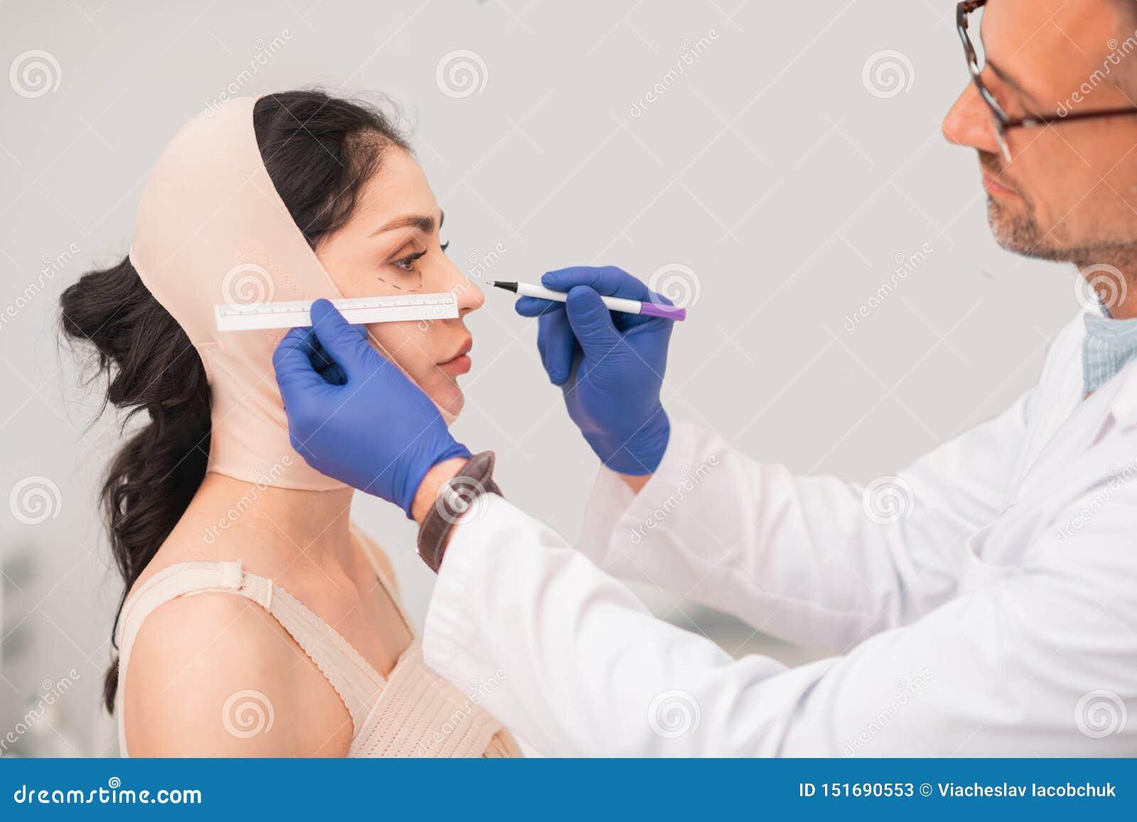 Chirurgien plasticien masculin barbu faisant des mesures de visage