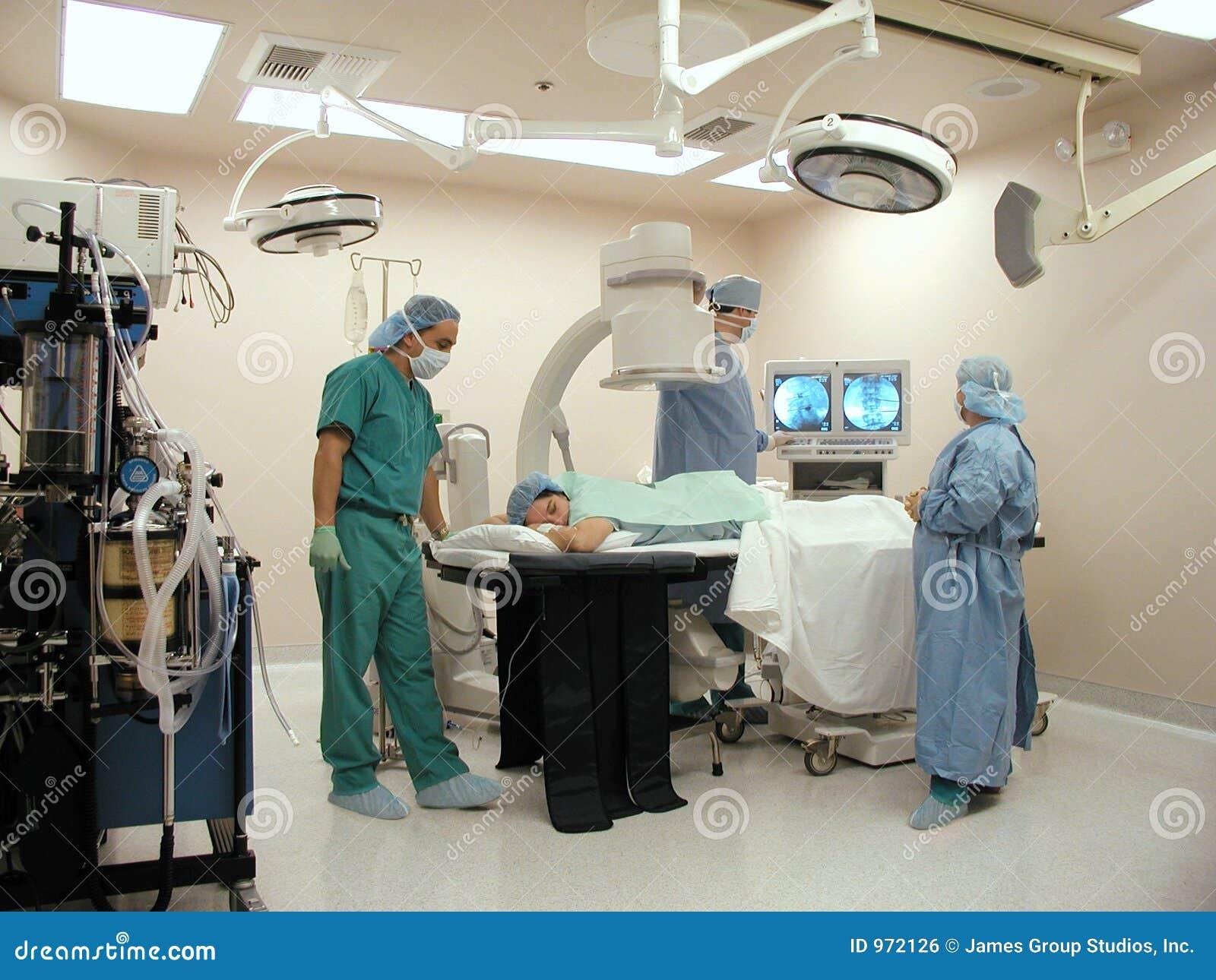 Chirurgiens avec le bras de C dans la salle d opération