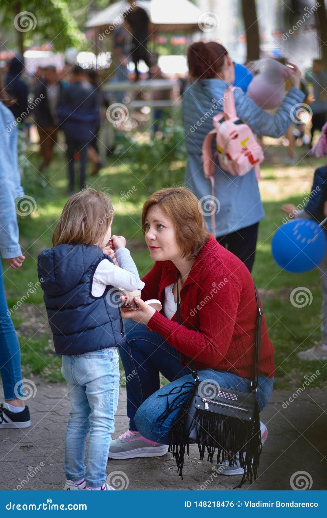 Chisinau, Δημοκρατία της Μολδαβίας - 10 Μαΐου 2019: το παγωτό διανέμεται δωρεάν, μια χαρούμενη γυναίκα δίνει το παγωτό παιδιών τη