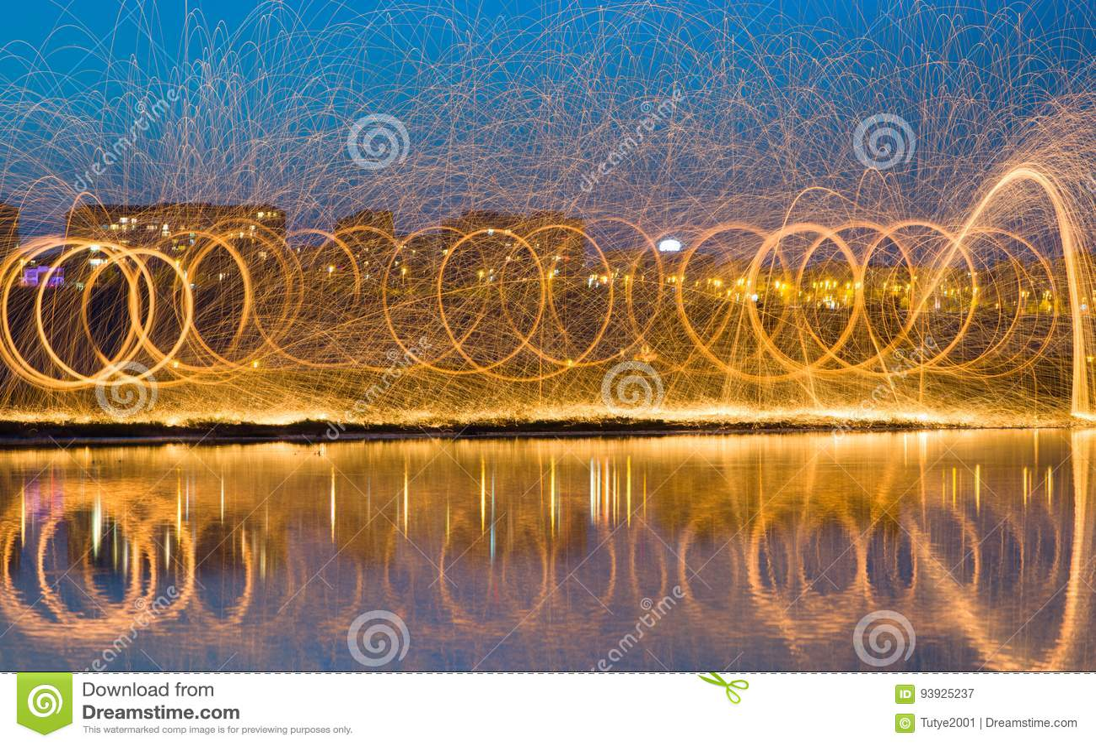 Chispas de oro calientes que vuelan de las lanas de acero ardientes de giro del hombre