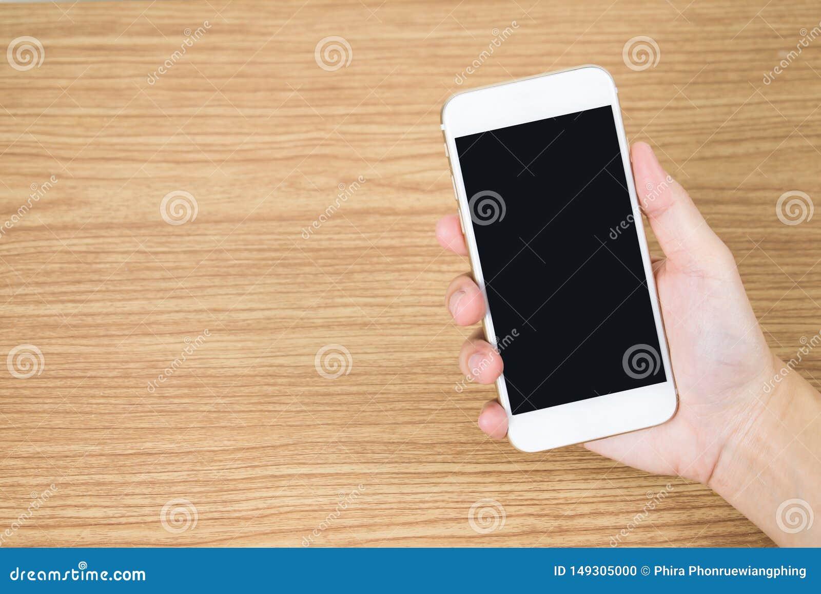 Chiuda fino alla mano che tiene il cellulare sulla vecchia tavola di legno nella stanza