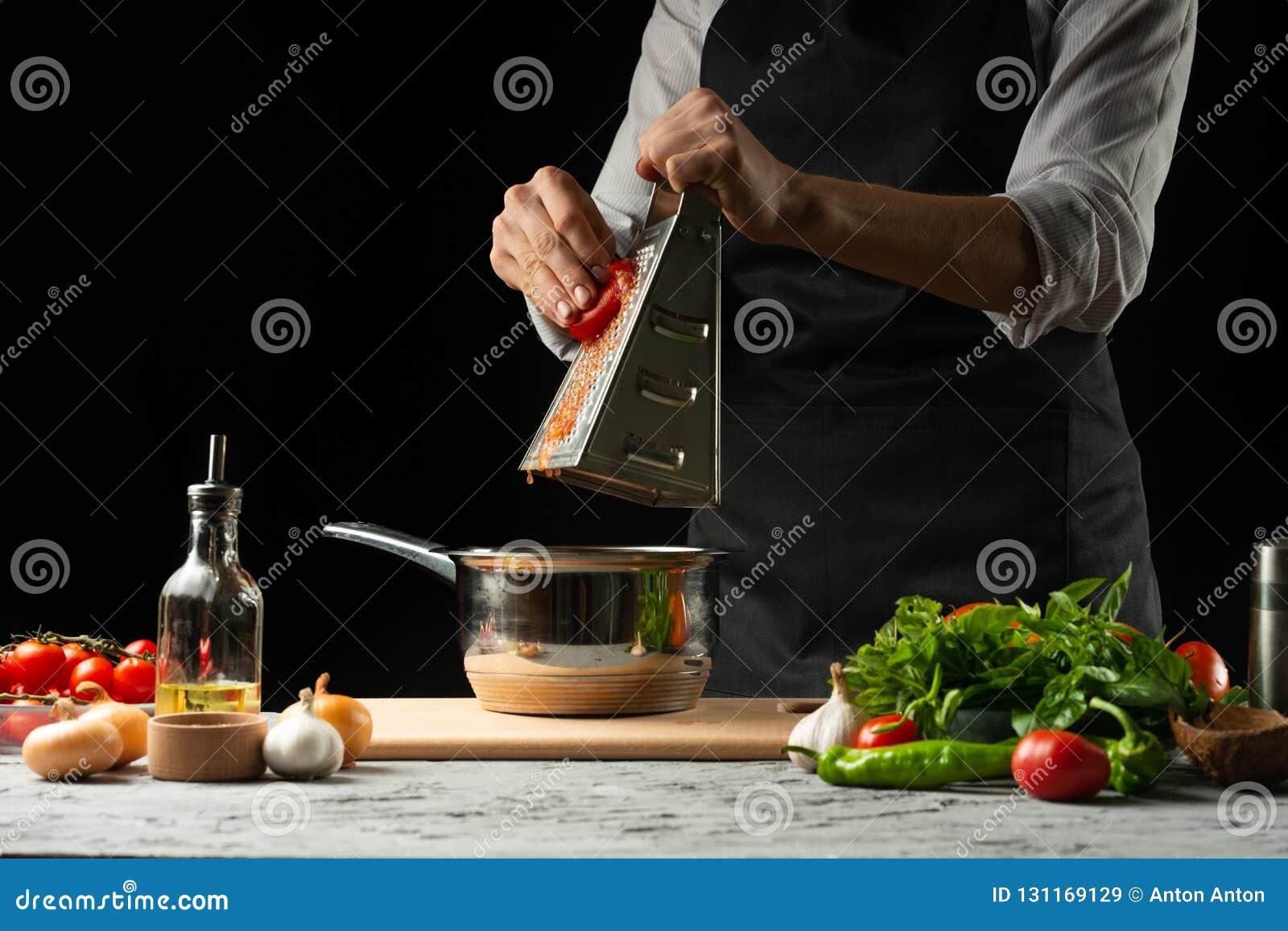 Chiuda il chef& x27; mani di s, preparanti una salsa al pomodoro italiana per i maccheroni Pizza Il concetto della ricetta di cot