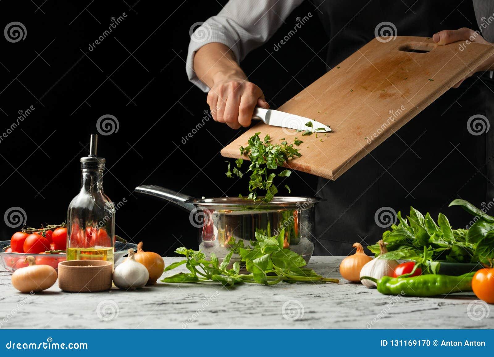Chiuda il chef& x27; mani di s, preparanti una salsa al pomodoro italiana per il mA