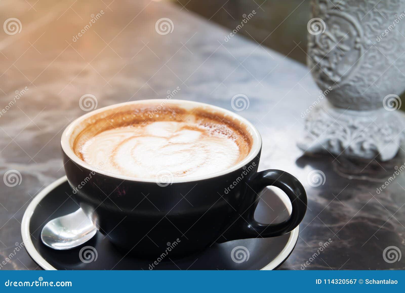 Chiuda su arte del latte del caffè in tazza nera su struttura di marmo, lusso